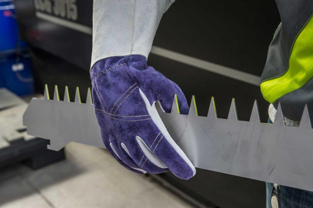 Leder-Schutzhandschuh greift in scharfkantiges Blech