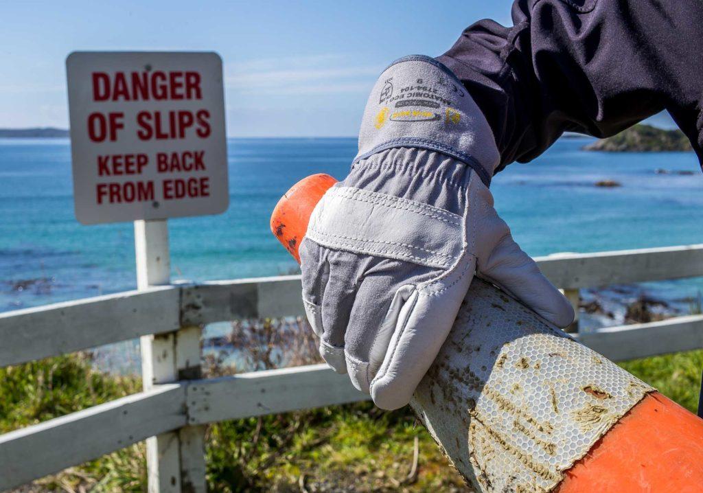 Handschuh mit Warnkegel an Küste