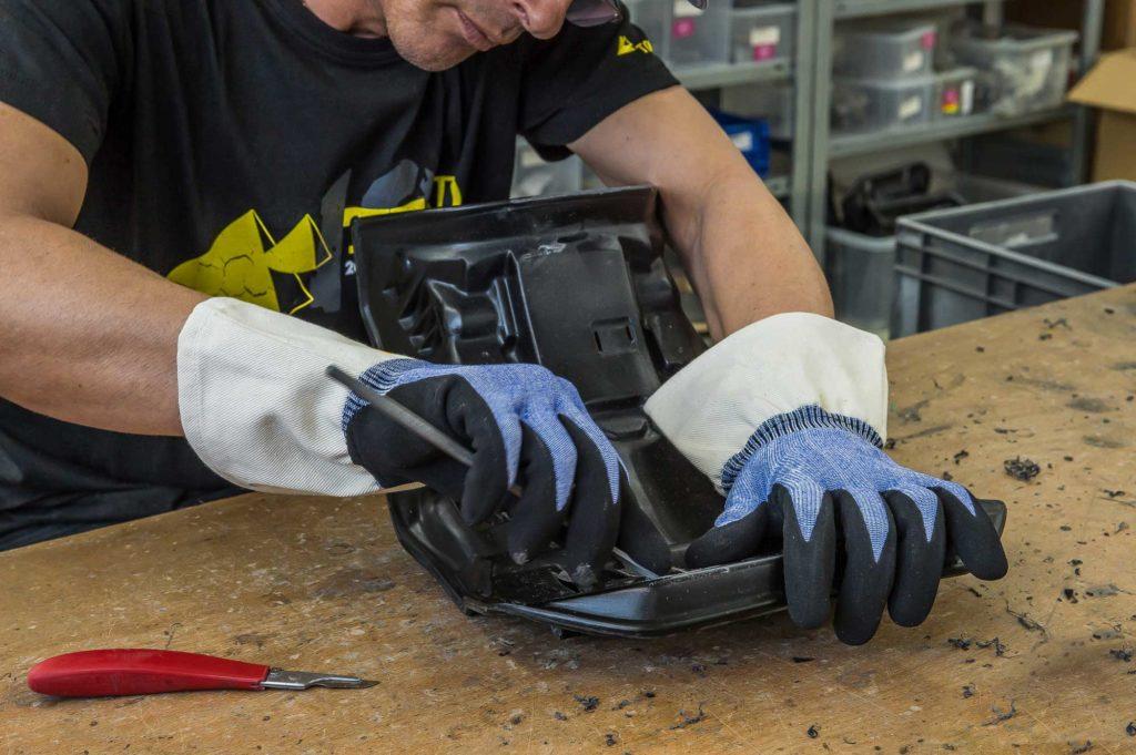 Entgraten eines Kunststoffteils mit Schnittschutz-Handschuhen