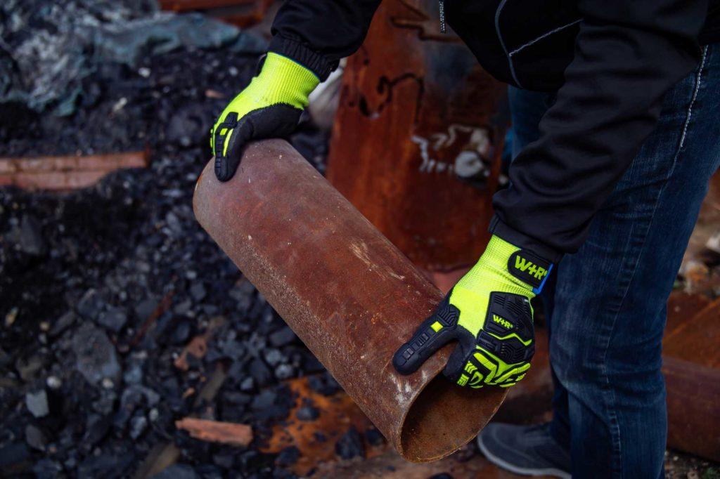 Rostiges Rohr wird mit gelben Schutzhandschuhen festgehalten
