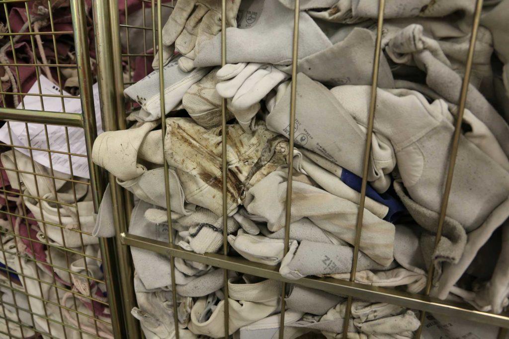 Verschmutzte Arbeitshandschuhe in Gitterwagen warten auf Reinigung